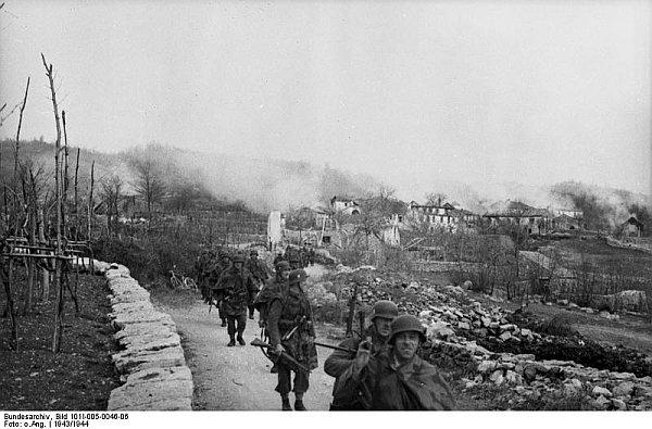"""Croazia, 5 aprile 1944. Soldati del I Battaglione del Polizeiregiment """"Bozen"""" si allontanano dal villaggio di Gornji Turki (nei pressi di Kastav /Castua) dopo averlo incendiato."""