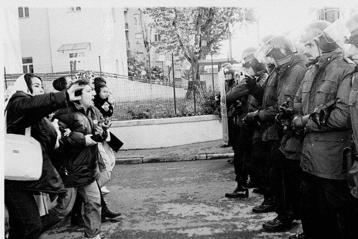 Bologna, 9 novembre 1998. In via Rimesse la polizia tenta lo sgombero alcune palazzine occupate da migranti nordafricani. Donne con bambini cercano di fermare i carabinieri in assetto antisommossa.