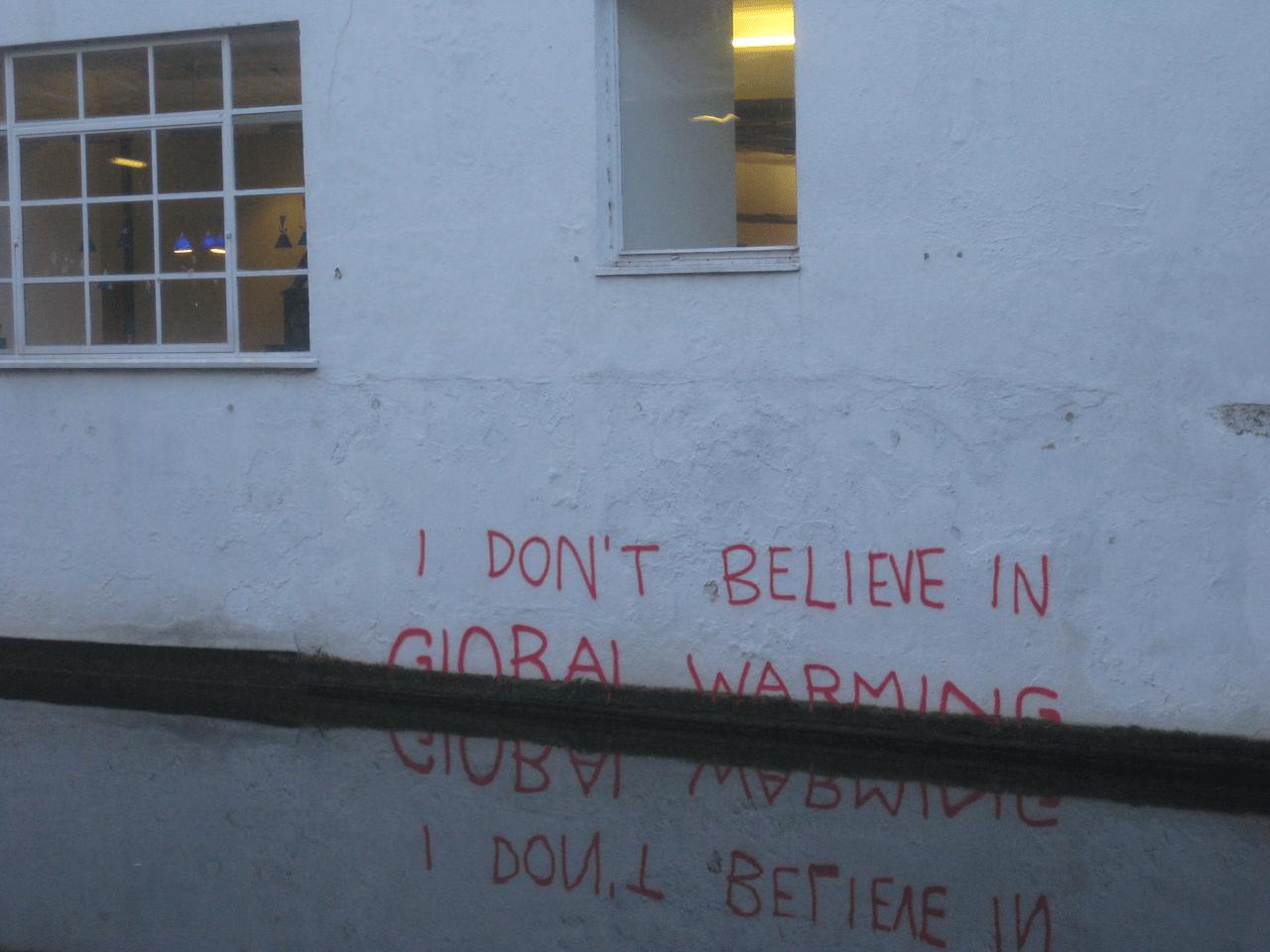 Scritta su un muro, semisommersa: «Non credo al riscaldamento globale».